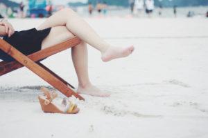 Sommer am Strand mit Beinen einer Frau